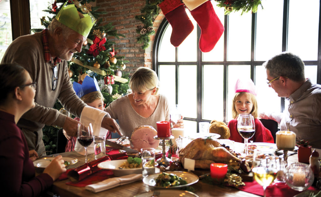 Picture of multigenerational family at the table for the holidays with Christmas decorations behind them.