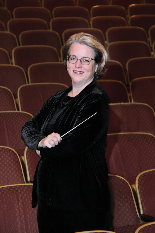 Kristin Roach standing in theater with her conductor baton