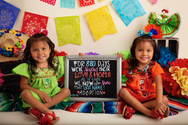 Two little girls smiling at camera with a sign that has details of their adoption